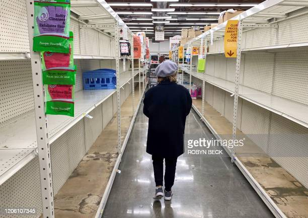 A shopper walks past empty shelves normally stocked with soaps sanitizers paper towels and toilet paper at a Smart Final grocery store March 7 2020...