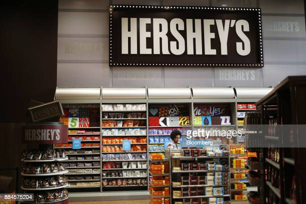 A shopper walks past Hershey Co candies displayed for sale inside of the company's Chocolate World visitor center in Hershey Pennsylvania US on...