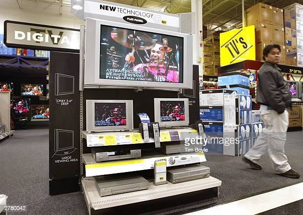 A shopper walks past new flatpanel television monitors December 3 2003 at a Best Buy store in Niles Illinois Electronics are the big items this...