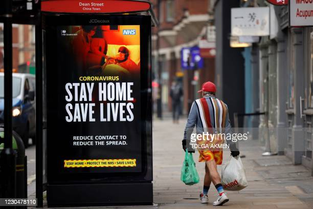 """Shopper walks past NHS signage promoting """"Stay Home, Save Lives"""" on a bus shelter in Chinatown, central London on January 8 as England entered a..."""