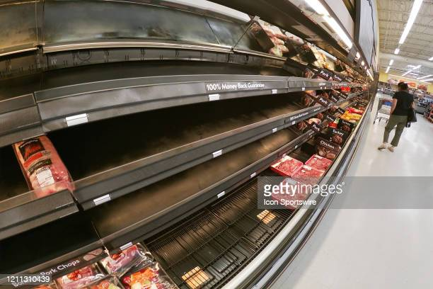 A shopper walks past the nearempty pork and turkey meat cases during the COVID19 Pandemic at Walmart Wednesday April 29 in Danville Illinois