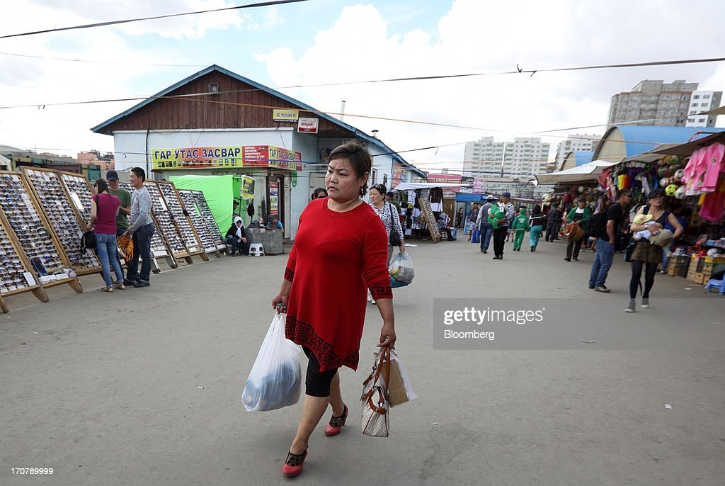 A shopper walks through a market in Ulaanbaatar, Mongolia, on Thursday, June 13, 2013. Mongolia, a country of almost 2.9 million people, is experiencing double-digit growth and new opportunities in the mining industry. Photographer: Tomohiro Ohsumi/Bloomberg via Getty Images