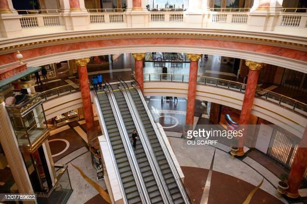 A shopper walks through a neardeserted Intu Trafford Centre shopping mall amidst the novel coronavirus COVID19 pandemic on the outskirts of...