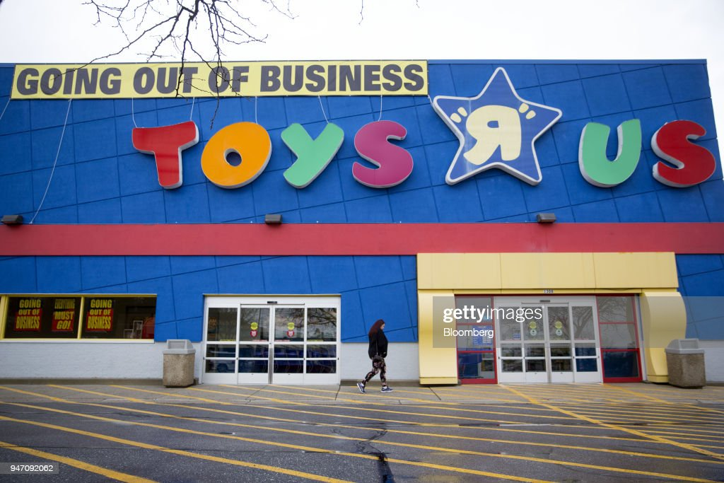 A shopper walks towards the entrance of a Toys R Us Inc. retail store in Frederick, Maryland, U.S., on Monday, April 16, 2018. Billionaire Isaac Larian, the toy marketer whose lineup includes Little Tikes and Bratz dolls, offered to save part of Toys 'R' Us from liquidation with an almost $900 million bid for stores in the U.S. and Canada. Photographer: Andrew Harrer/Bloomberg via Getty Images