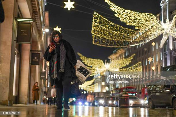 A shopper walks under Christmas lights on December 17 2019 in London England The Centre for Retail Research have announced that UK shoppers are...
