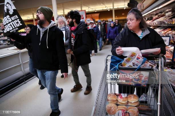 A shopper watches as Jim Carvalho left marches with fellow members of the United Food and Commercial Workers Union and their supporters during a...