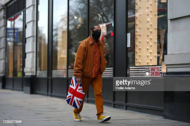 Shopper wearing a face mask carries a Union Jack shopping bag along Oxford Street on December 12, 2020 in London, England.
