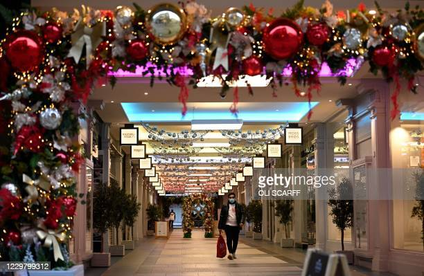 A shopper wearing a face mask due to the COVID19 pandemic walks through the Christmasdecorated Royal Exchange shopping arcade in the centre of...