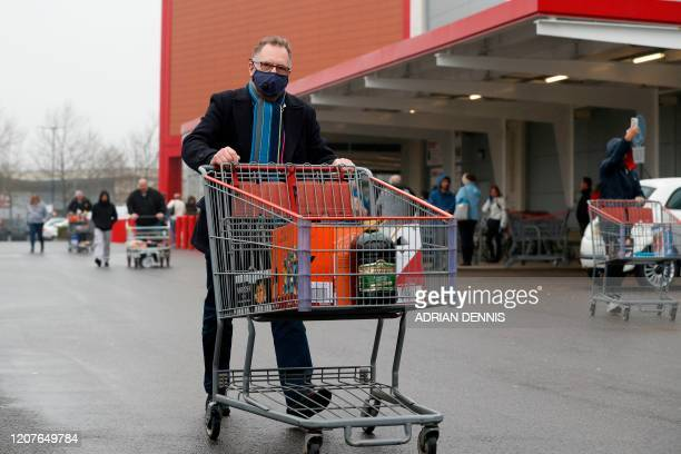 Shopper wearing a face mask leaves a Costco members wholesale outlet in Farnborough, west of London, on March 19, 2020. - Britain's supermarkets...