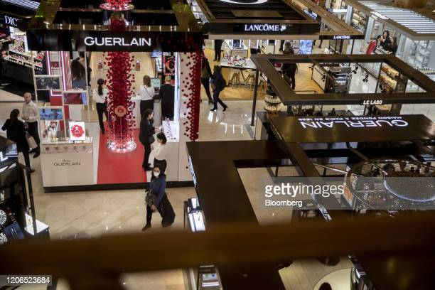A shopper wearing a face mask passes a Guerlain Inc cosmetics sales boutique in the Galeries Lafayette SA department store in Paris France on Tuesday...