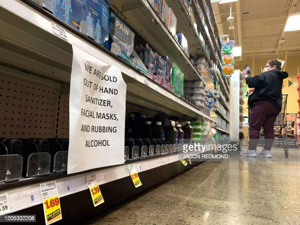 A shopper wearing a mask is pictured near a sign advising outofstock sanitizer facial masks and rubbing alcohol at a store following warnings about...