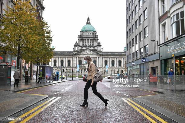 Shopper wearing a mask walks past Belfast City Hall on October 14, 2020 in Belfast, Northern Ireland. The Northern Ireland government, which largely...