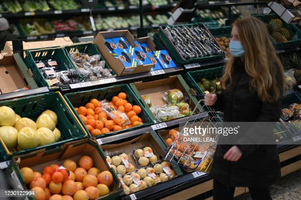Shopper wearing a protective face covering to combat the spread of the coronavirus, browses for fruit and vegetables in a Tesco supermarket in London...