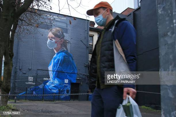 Shopper wearing a protective face covering walks past a mural of a NHS worker on a wall in north Manchester, north-west England on November 5 as...