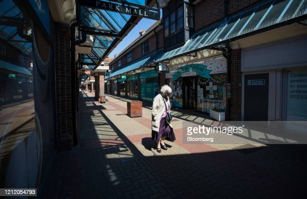 A shopper wearing a protective face mask passes through a shopping mall in Ashford UK on Wednesday May 6 2020 Shopping malls will be worst affected...