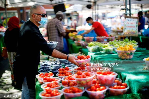 Shopper wearing a protective face mask selects a bowl of tomatoes as he shops at an outdoor street market in Walthamstow, east London on May 28...
