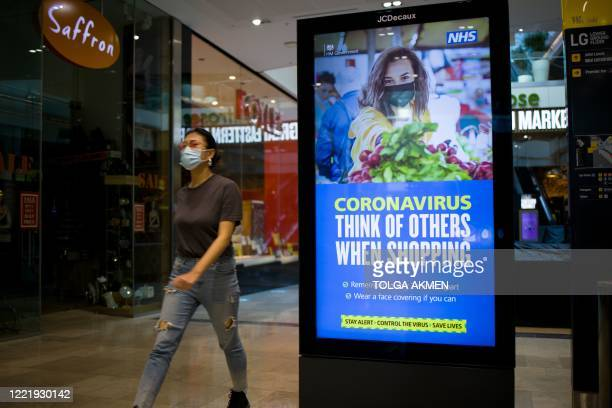A shopper wearing a protective face mask walks past Government advice being displayed on an advertisement board in Westfield shopping centre in...