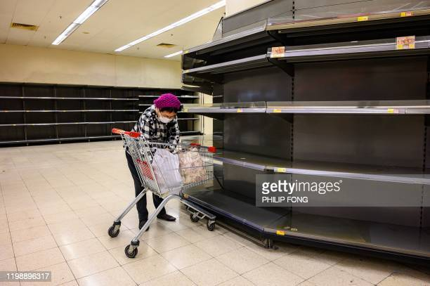 TOPSHOT A shopper wearing a protective facemask sorts items in her trolley as she stands next to bare supermarket shelves usually stocked with toilet...