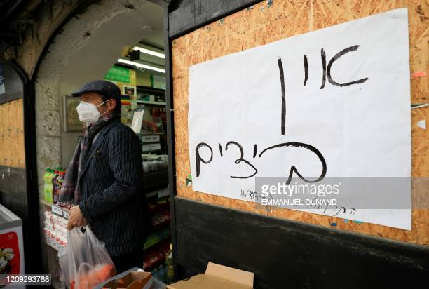A shopper wearing a protective mask precaution against COVID19 coronavirus disease exits a food market in Jerusalem on April 6 while walking past a...
