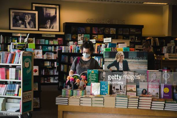 Shopper wearing a protective mask reads inside a Books-A-Million Inc. Store in the re-opened Anderson Mall in Anderson, South Carolina, on Friday,...