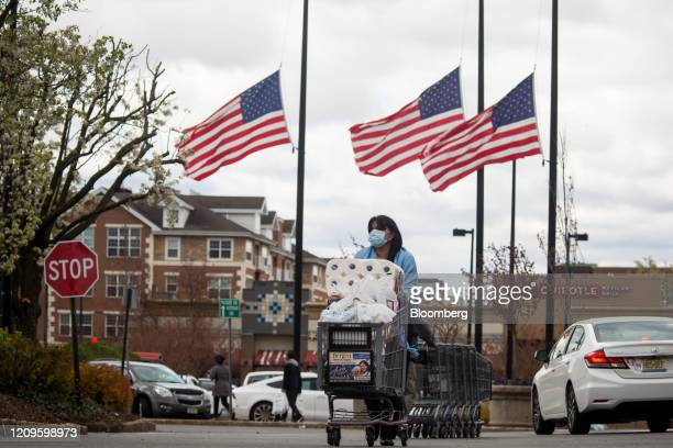 Shopper wearing a protective mask walks past American flags at half-mast in a ShopRite Holdings Ltd. Grocery store parking lot in Englewood, New...