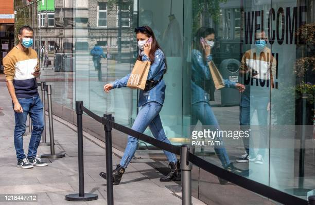 Shopper wearing PPE , including a face mask as a precautionary measure against COVID-19, exits a re-opened Zara shop in Grafton Street in central...