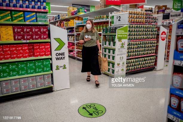 A shopper wearing PPE of a face mask or covering as a precautionary measure against spreading COVID19 walks past a floor sticker advising customers...