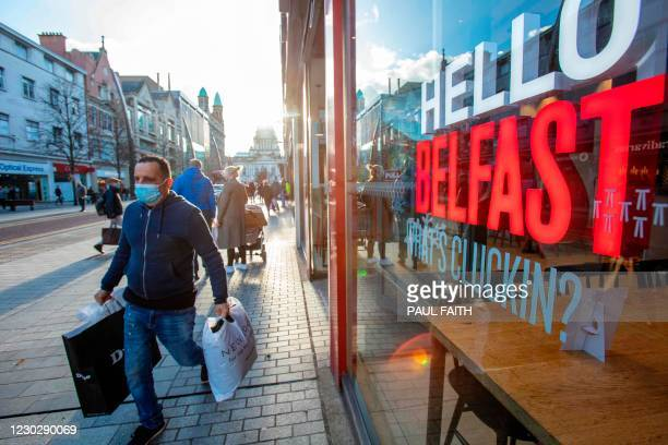 Shopper wearing protective a face covering to combat the spread of the coronavirus, walks through Belfast city centre on Christmas Eve, December 24,...