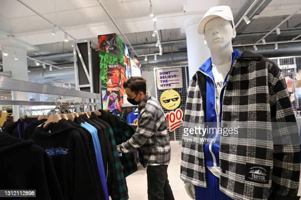 Shopper wears a face covering as as he looks at clothes in Selfridges store on Oxford Street on April 12, 2021 in London, England. England has taken...