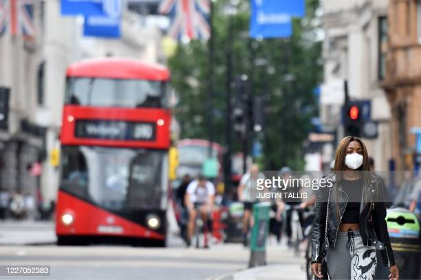 A shopper wears a mask as a precaution against the transmission of the novel coronavirus as she walks along Oxford Street in London on July 14 2020...
