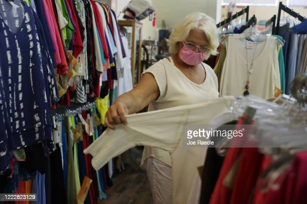 A shopper wears a protective mask while browsing through the Island Cotton Company store as the state of Florida enters phase one of the plan to...