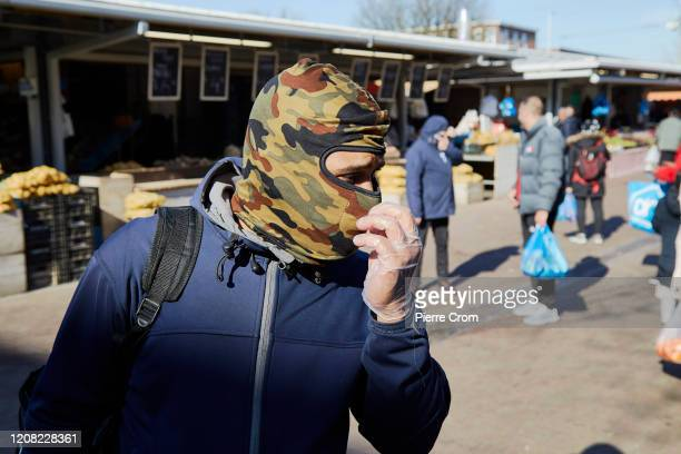 A shopper wears gloves and a mask at The Hague market one of the largest market in Europe amid the worsening COVID19 virus pandemic on March 25 2020...