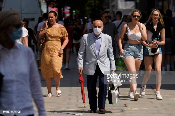 Shopper with a face mask on walks with other pedestrians on Oxford street in central London on July 19, 2021 as coronavirus restrictions are lifted....
