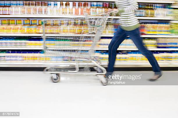 shopper with in a hurry with cart in aisle - chores stock photos and pictures
