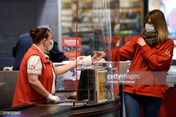 A shopper with protective mask at the cashier in a supermarket on April 01 in Vienna Austria Starting today the Austrian Government requires...