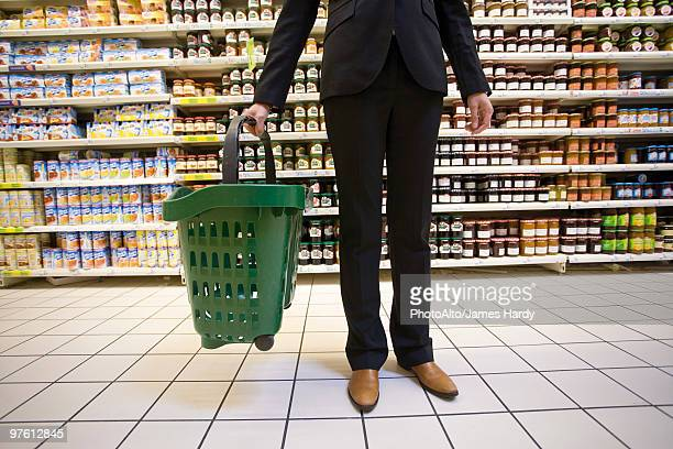 Shopper with shopping basket standing in supermarket aisle