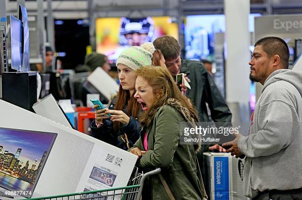 A shopper yawns as she stands in line to purchase electronics at a Best Buy on November 26 2015 in San Diego California Although Black Friday sales...
