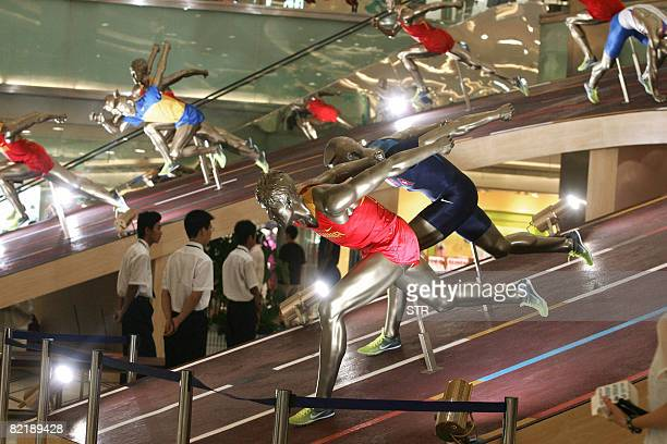 Shoppers admire a display of various 2008 Beijing Olympic Games jerseys and uniforms at a shopping mall in Beijing August 6 2008 Beijing is expecting...