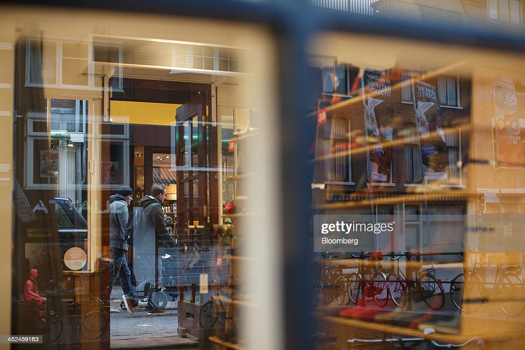 Shoppers and bicycles are seen reflected in a shop window in Utrecht, Netherlands, on Friday, Nov. 29, 2013. European government bonds were little changed as investors showed a muted reaction to Standard & Poor's decision to raise its outlook on Spain's debt and strip the Netherlands of its top credit rating. Photographer: Jasper Juinen/Bloomberg via Getty Images