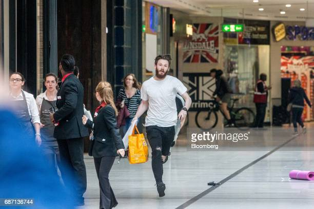 Shoppers and employees evacuate the Arndale shopping mall in Manchester UK on Tuesday May 23 2017 At least 22 people were killed in a suicide bombing...