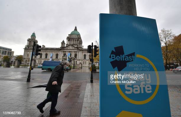 Shoppers and office workers walk past Belfast City Hall on October 14, 2020 in Belfast, Northern Ireland. The Northern Ireland government, which...