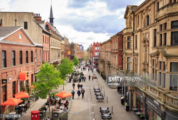 shoppers and other pedestrians walking through a street in leeds, west yorkshire - leeds stock pictures, royalty-free photos & images