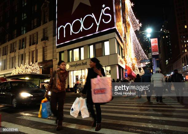 Shoppers and pedestrians cross 34th Street outside of Macy's Herald Square department store after 10pm December 22 2009 in New York City Macy's is...