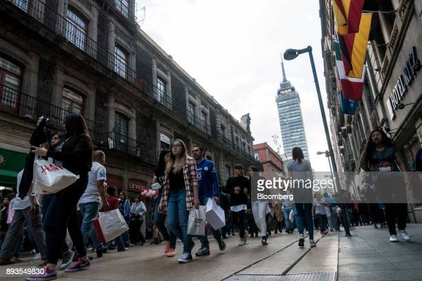 Shoppers and pedestrians pass in front of the Torre Latinoamericana in Mexico City Mexico on Monday Nov 20 2017 The National Institute of Statistics...