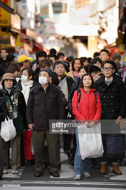 Shoppers and pedestrians wait to cross a road at Ameyoko market in Tokyo Japan on Saturday Dec 26 2015 Japan's consumer prices rose slightly in...