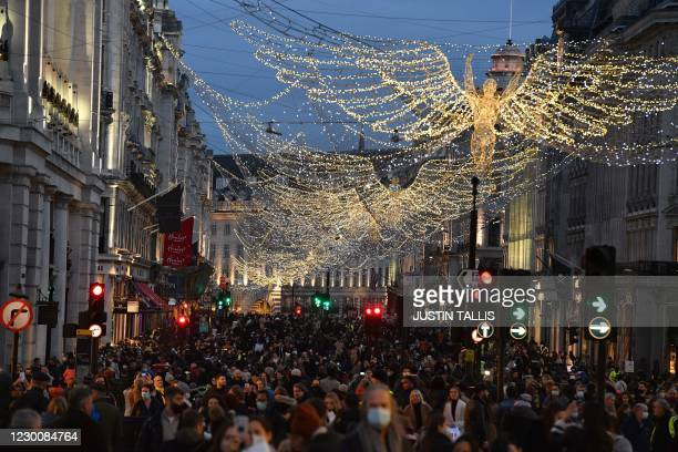 Shoppers and pedestrians walk along Regent Street in London on December 12 as with under two weeks to Christmas, people take advantage of the easing...
