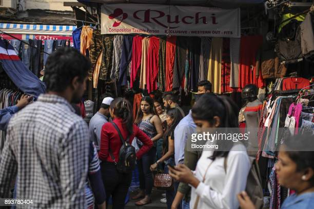 Shoppers and pedestrians walk past roadside stalls in Mumbai India on Friday Dec 15 2017 India's inflation surged past the central bank's target...