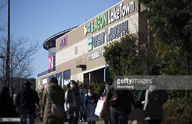 Shoppers and pedestrians walk past the Aeon Lake Town shopping mall operated by Aeon Retail Co a unit of Aeon Co on the first day of the New Year...