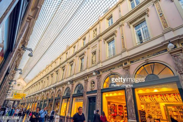 Shoppers and tourists strolling under the glass-roofed of Galeries Royales Saint-Hubert, one of several Arcade galleries in Brussels, Belgium