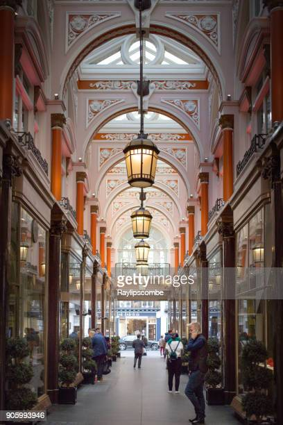 Shoppers and tourists walking through The Royal Arcade, London, UK.